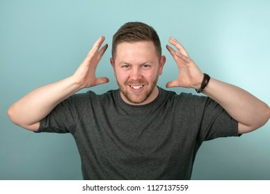 Frustrated angry man snarling and gesturing with his hands either side of his head over a grey background