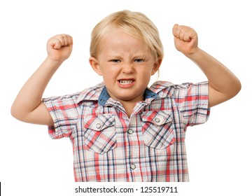 A frustrated and angry young boy with fists raised in the air and pulling a face. Isolated on white.