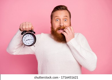 Frustrated anxious guy hold clock see time shocked he miss work study deadline feel panic bite nails wear sweater isolated over pastel color background