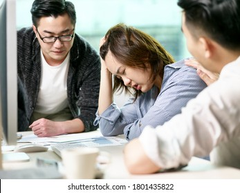 frustrated asian businesswoman getting comfort from colleagues while discussing business in office