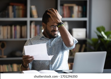 Frustrated biracial male student sit at desk feel distressed with bad news in paper letter, unhappy African American man stressed by dismissal notice or negative reply in post correspondence or notice