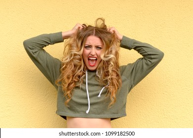 Frustrated blond woman tearing at her long wavy hair and yelling to vent her feelings over a yellow studio background