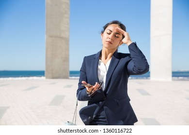 Frustrated business lady suffering from heat. Young woman in formal suit touching head with closed eyes. Sunstroke or headache concept