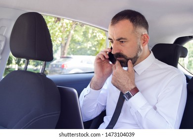 Frustrated business man / employee  talking on mobile phone while sitting in the back seat of car. He has a problem and doesn't know how to solve it.