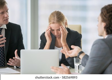 Frustrated business people sitting at the table in office, arguing while discussing project. Their female colleague covering her face with hands looking exhausted and ill. Business problem concept