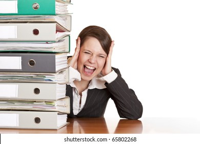 Frustrated business woman cries in office behind behind a folder stack. Isolated on white background.