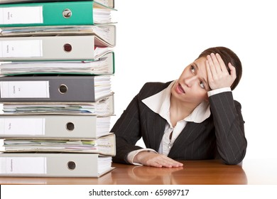 Frustrated business woman in office looks at unbelievable folder stack. Isolated on white background.