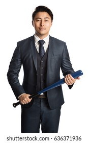 Frustrated businessman in a blue suit and tie standing against a white background holding a baseball bat.
