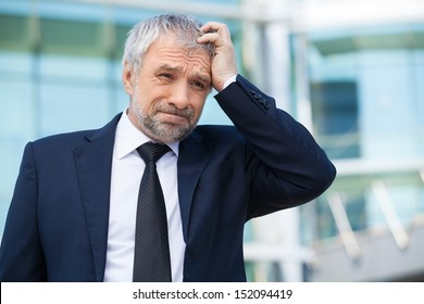 Frustrated businessman. Depressed senior man in formalwear holding hand in hair and looking away