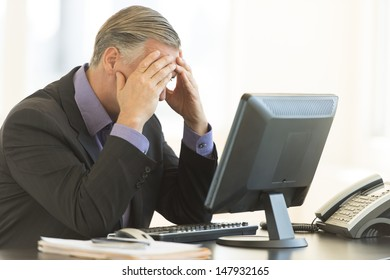 Frustrated businessman with head in hands sitting at office desk