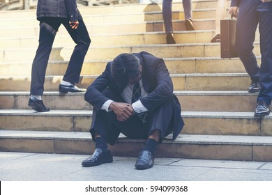 Frustrated Businessman Making a Mistake in his Business, Sitting on Stairs Between Many Crowd of People in Business Area. Man Feeling Stressed on his Crisis Situation.