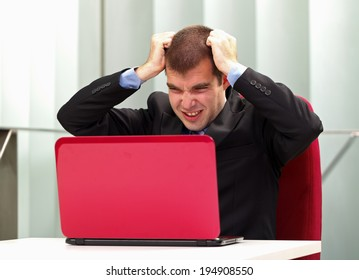 A frustrated businessman sitting in his office, in front of his laptop