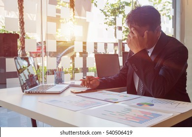 Frustrated businessman sitting at office desk