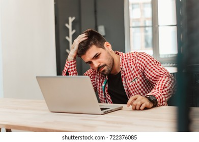 Frustrated businessman sitting on desk with hand on head in office.