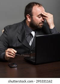 Frustrated businessman working on laptop