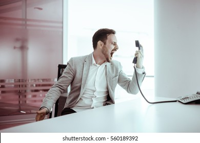 Frustrated businessperson angrily yelling at phone