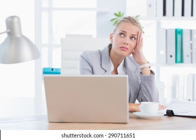 Frustrated businesswoman with head in hand in her office