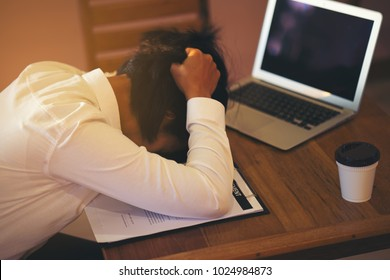 Frustrated businesswoman holding head in hands sitting at office desk covered , feeling tired after unproductive work, giving up, creative crisis, no motivation, lack of ideas,Stressful careers storie