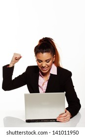 Frustrated businesswoman punching her laptop sitting at her desk with her fist raised in the air and the computer open in front of her
