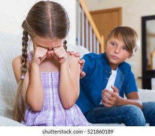 Frustrated children having serious fight in livingroom at home