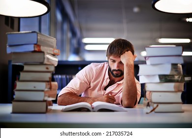 Frustrated college male student studying poorly at late evening, night before exam, male student with pile of books study hard for exam in high school, tired and bored to study hard for exam