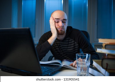 frustrated college student studying poorly at late evening, night before exam, funny night procrastination concept