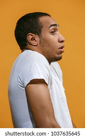 Frustrated concept. Frustrated Afro-American is looking frightenedly. Young emotional man. Human emotions, facial expression concept. Profile . Studio. Isolated on trendy orange