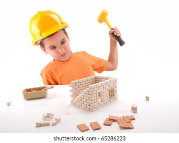 Frustrated cute boy destroying brick house he built  isolated on white - a series of BUILDING A HOUSE  images.
