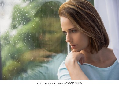 frustrated cute girl sitting in front of window