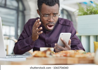 Frustrated dark skinned male looks desperately into screen, reads information on smart phone, sits in coffee shop, uses laptop computer for making business report. People, negative emotions concept