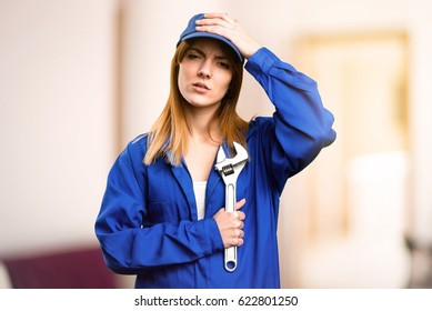 Frustrated delivery woman on defocused background