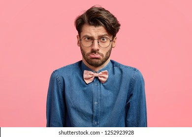Frustrated displeased man with trendy hairstyle, purses lower lip, has indecisive dissatisfied facial expression, wears denim shirt and bowtie, stands alone against pink studio wall. Negative emotions