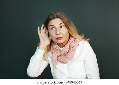 Frustrated elderly woman suffering from deafness, trying hard to hear something. Curious senior female eavesdropping, holding hand at her ear and listening attentivel. Difficulty in hearing