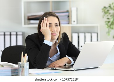 Frustrated executive posing looking at camera on a desktop at office