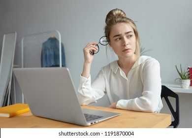 Frustrated exhausted young woman blogger dressed in white blouse holding round eyeglasses and looking away with worried expression, searching for inspiration, trying to write article for her blog