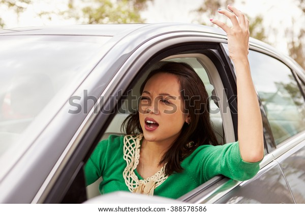 Frustrated female Asian driver in a car
