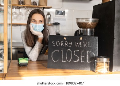 Frustrated female owner wearing medical mask leaned on bar counter in closed cafe, small business lockdown due to coronavirus, bankrout concept