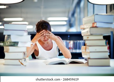 Frustrated female student sitting at the desk with a huge pile of study books in university library, young asian college student at hard exam preparation in study hall looking tired and weary