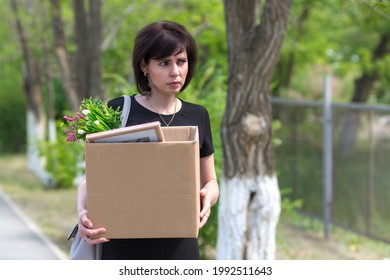 A frustrated fired woman with a box in her hands walks through the city. - Shutterstock ID 1992511643