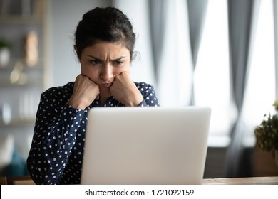 Frustrated frowning young indian female student looking at laptop monitor, feeling dissatisfied with received email. Head shot unhappy hindu woman reading bad news notification, solving problem.