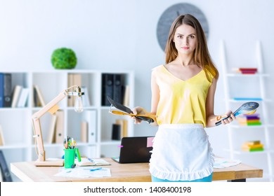Frustrated girl in apron is standing and holding kitchenware, modern office on background. Unhappy woman forced to cook in kitchen because of sexist views in society. Gender inequality concept.