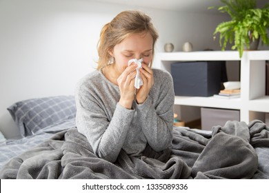 Frustrated girl catching cold, resting in bed, covering nose with tissue and sneezing. Young woman suffering from snuffle. Cold or flu concept