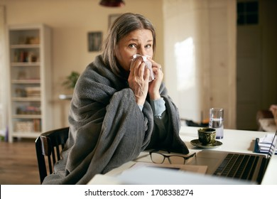 Frustrated gray haired retired woman sitting at table using portable computer to contact physician online, blowing nose, suffering from flu or cold. Technology, health care and elderly people concept