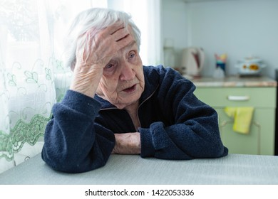 Frustrated gray-haired old woman sitting at home at the table.