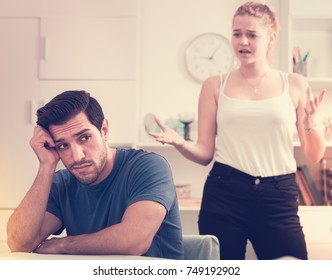 Frustrated guy sitting at home table on background with dissatisfied girlfriend