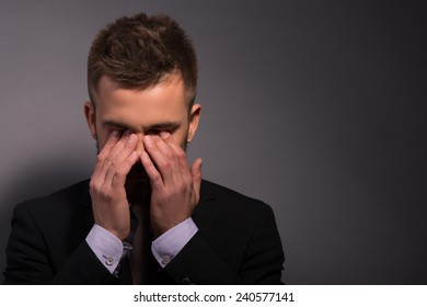 Frustrated handsome. Depressed young businessman in formalwear holding hands on eyes thinking of bad news while stranding against grey background