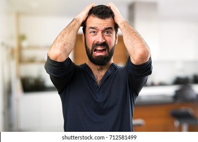 Frustrated handsome man with beard inside house