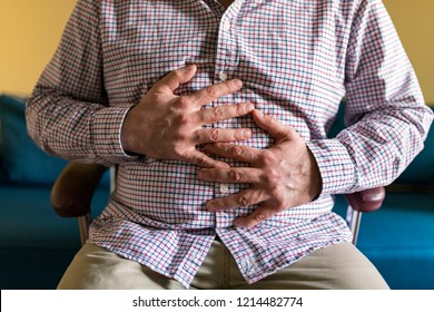 Frustrated Handsome Man Hugging His Belly In Pain. Disturbed Male Having Pain In Stomach