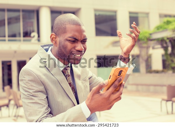 Frustrated handsome young business man in suit receiving bad news message on mobile smart phone standing outdoors outside corporate office