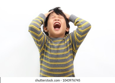 Frustrated Little Asian boy screaming with both hands holding his head isolated on white background.